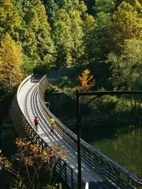 Cyclists Cross a Bridge on the Greenbrier Trail in West Virginia by Skip Brown