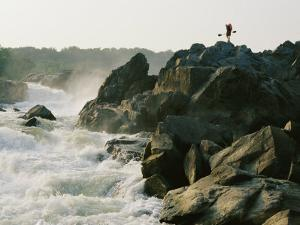 Kayaker Carries Boat up the Rocks of Great Falls on the Potomac River by Skip Brown