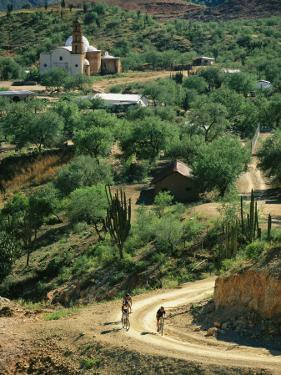 Mountain Bikers Ride out from Batopillas, Satevo Mission Behind by Skip Brown