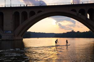 Paddleboarders Glide on the Potomac River under the Key Bridge in Georgetown by Skip Brown