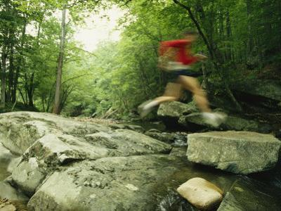 Panned View of Man Leaping over Rocky Stream on the Appalachian Trail by Skip Brown