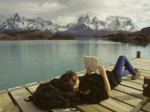 Woman Relaxes on a Dock While Reading a Book by Skip Brown