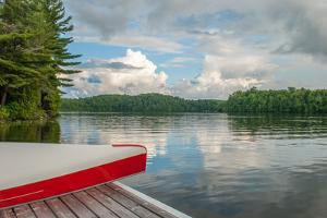 Red and White Canoe by a Lake with a Dramatic Sky by slapointe