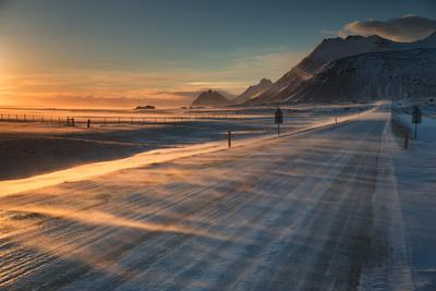 https://imgc.allpostersimages.com/img/posters/snow-blows-across-an-icelandic-road-at-sunrise-with-mountains-looming-in-the-distance_u-L-Q12WM0C0.jpg?artPerspective=n