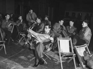 Songwriter Irving Berlin Reading Newspaper as Others Sit around Talking