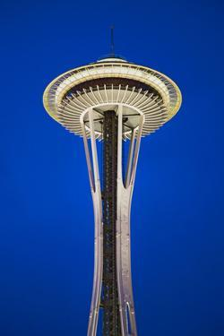 Space Needle in Seattle, Washington at dusk in deep blue sky; it is a major landmark and a symbo...