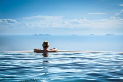 Woman Relaxing in Infinity Swimming Pool on Vacation by Splendens