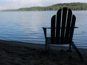 An Adirondack Chair Silhouetted by a Lake by Stacy Gold