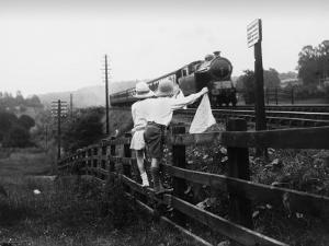 Two Children Stand on a Fence and Wave a Handkerchief at a Passing Steam Train by Staniland Pugh