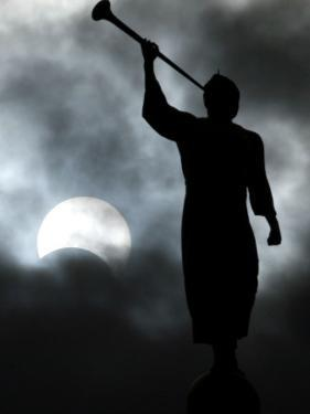 Statue is Seen Against a Cloudy Sky and a Partial Solar Eclipse in Bogota, Colombia