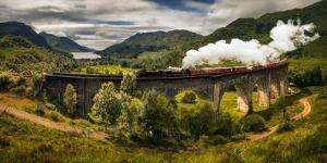 Steam train moving on old bridge, Scotland