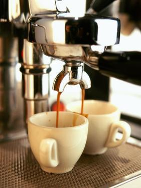 Espresso Running out of Espresso Machine into Two Cups by Stefan Braun