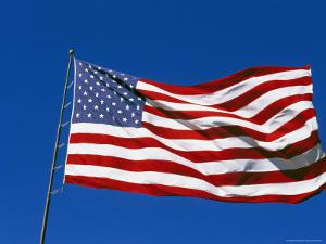 American Flag Flies in a Clear Blue Sky by Stephen Alvarez