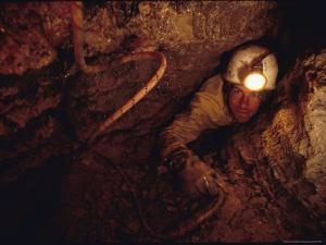 Caver Goes Through Very Tight Squeeze by Stephen Alvarez