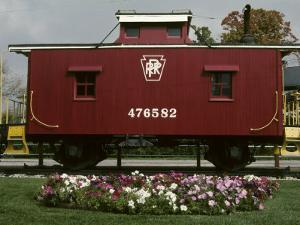 A Bright Red Caboose and a Flower Bed Compete for Vivid Color by Stephen St. John