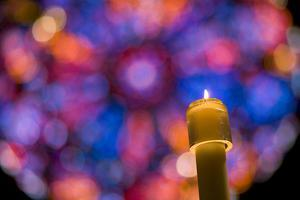 A Christmas Candle Glows Against a Rose Window Backdrop by Stephen St. John