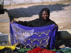 A Nubian Woman Sells Colorful Scarves on the Street by Stephen St. John