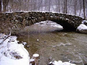 An Old Stone Bridge Over Rock Creek During a Snow Storm by Stephen St. John