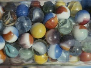 Close View of Colorful Glass Marbles in a Jar by Stephen St. John