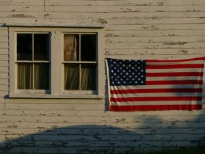Evening Light on an American Flag on the Side of an Old Barn by Stephen St. John