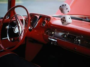 Fuzzy Dice and Cherry Red Interior of a Classic Car by Stephen St. John