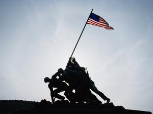 The Iwo Jima Memorial Silhouetted with Flag Flying by Stephen St. John