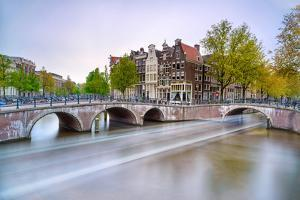 Amsterdam. Bridge and Water Canal. Boat Light Trail on Sunset. Holland or Netherlands. by stevanzz