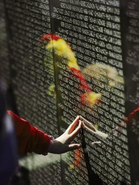 A Hand Reaches out to Touch a Name on the Vietnam Wall by Steve Raymer