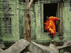 A Monk Emerges from the Doorway of an Angkor Wat Temple by Steve Raymer