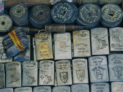 A Tray Full of War Memorabilia Engraved Zippo Lighters, Dog Tags, Bullets, and Ancient Coins