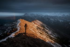 A Male Photographer Capturing a Sunrise Along the Rocky Mountain Front, Sawtooth Range, Montana by Steven Gnam
