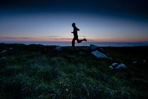 A Young Woman on a Sunset Run Along a Wild Stretch of the California Coastline by Steven Gnam