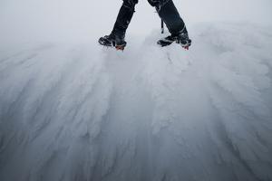 Mountaineer Walks Along a Wind Swept Ridge in Western Montana by Steven Gnam