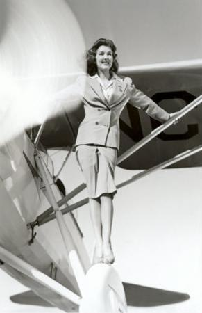Stewardess Balancing on Plane Wheel