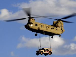 A U.S. Army CH-47 Chinook Helicopter Transports a Humvee by Stocktrek Images