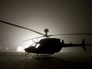 Illumination from the Bright Light Silhouettes of OH-58D Kiowa Helicopter During Thick Fog by Stocktrek Images