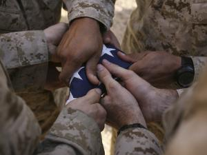 Marines Fold an American Flag after It was Raised in Memory of a Fallen Soldier by Stocktrek Images
