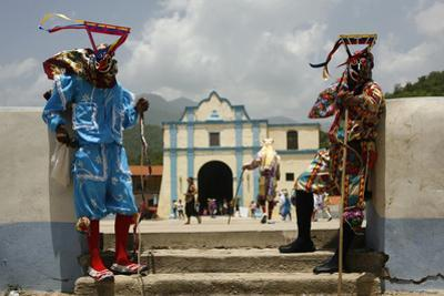 Masked Revellers Stand in Front of the Church