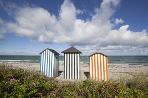 Colourful beach huts on pebble beach with blue sea and sky with clouds, Rageleje, Kattegat Coast, Z by Stuart Black
