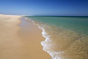 Empty white sand beach and breaking waves of crystal clear sea, Ilha do Farol, Culatra barrier isla by Stuart Black
