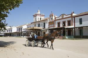 Horse and carriage riding along sand streets with brotherhood houses behind, El Rocio, Huelva Provi by Stuart Black