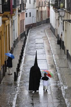 Penitents During Semana Santa (Holy Week) Along Rainy Street, Seville, Andalucia, Spain, Europe by Stuart Black