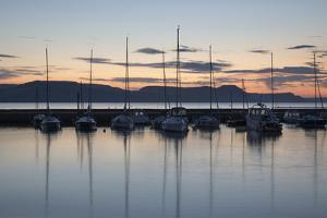 Yachts moored in The Cobb with Jurassic Coast and Golden Cap at sunrise, Lyme Regis, Dorset, Englan by Stuart Black