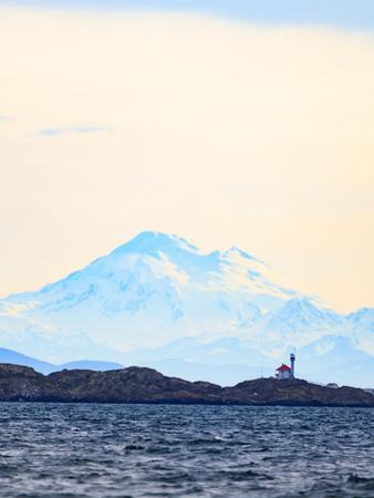 Discovery Island Lighthouse, Victoria, B.C. against Mt. Baker by Stuart Westmorland