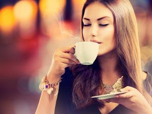 Beautiful Girl Drinking Tea or Coffee in Café by Subbotina Anna