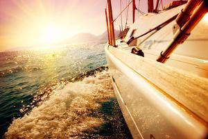 Yacht Sailing against Sunset. Sailboat. Yachting. Sailing. Travel Concept. Vacation by Subbotina Anna