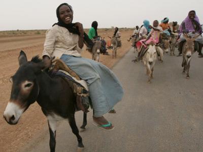 Sudanese Women Ride Donkeys at the Entrance of the Zamzam Refugee Camp