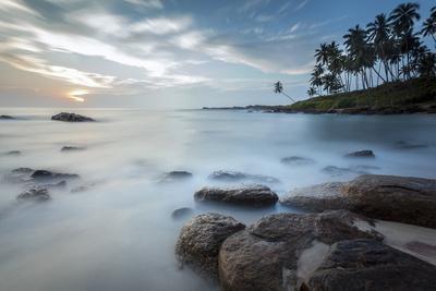 https://imgc.allpostersimages.com/img/posters/sunrise-at-a-secluded-lagoon-with-rocks-and-palm-trees-framing-the-view_u-L-PQ8NWZ0.jpg?p=0