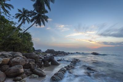 https://imgc.allpostersimages.com/img/posters/sunrise-at-a-secluded-lagoon-with-rocks-and-palm-trees-framing-the-view_u-L-PQ8NXB0.jpg?p=0