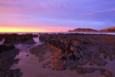 https://imgc.allpostersimages.com/img/posters/sunrise-casts-a-red-pink-hue-on-rocks-of-a-beach-looking-towards-nugget-point_u-L-PQ8OVZ0.jpg?p=0